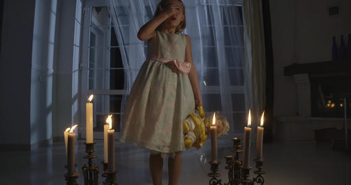 Portrait of scared Caucasian little girl in beautiful dress holding doll Live Action