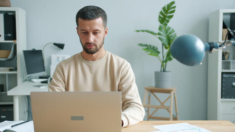 Serious businessperson typing using laptop computer indoors in office room Live Action
