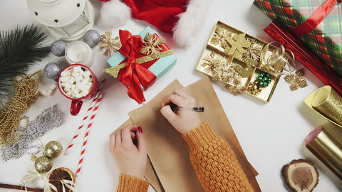 Female hand writing a gift list on wooden table with gifts, wrapping paper, red Live Action