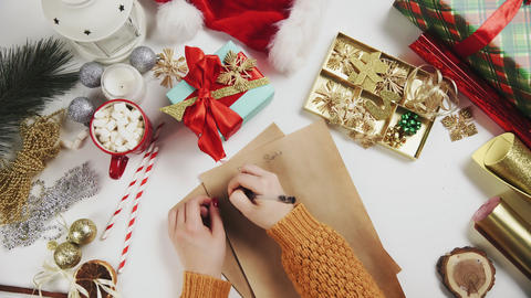 Female hand writing a gift list on wooden table with... Stock Video Footage