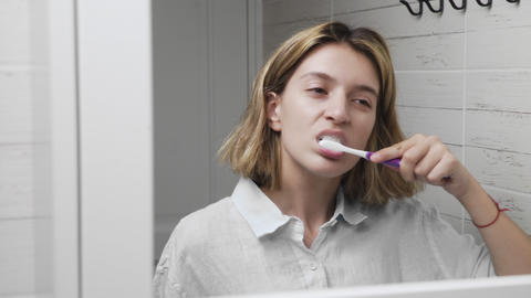 Young beautiful girl with toothbrush. Brushing teeth. Closeup of woman brushing Live Action
