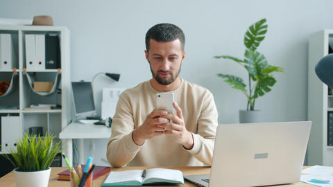 Carefree middle-aged man using smartphone smiling working in office at work Live Action