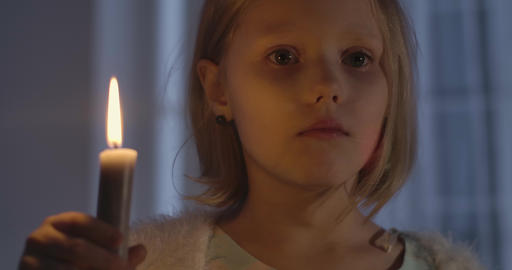 Close-up face of little Caucasian girl holding candle and shaking her head Live Action