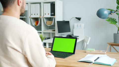 Businessperson looking at green screen chroma key laptop working in modern Live Action