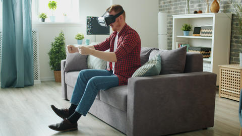 Carefree student wearing virtual reality glasses enjoying driving game at home Live Action