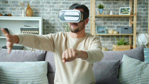 Funny man having fun with ar goggles in apartment moving arms entertaining Live Action