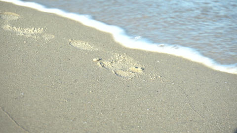 Footprint in the sand. The wave washes away the footprint. The waves come to the Live Action