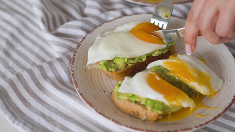 Slicing toast with avocado and egg. Healthy vegan breakfast Live Action