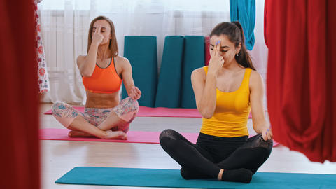 Yoga - two women sitting on the mats and doing breathing exercises with two Live Action
