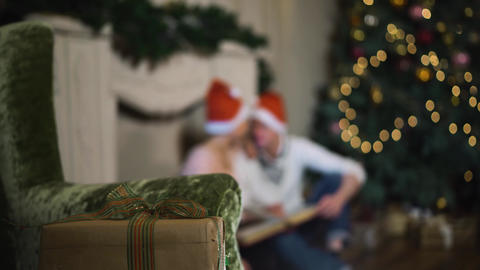 Couple celebrating Christmas consider an album of lovely photos Live Action