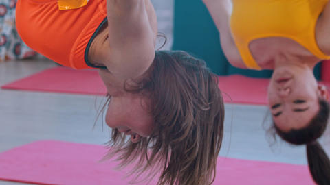 Aerial yoga - an athletic woman hanging upside down in hammock for yoga Live Action