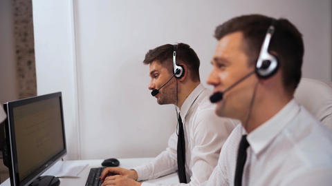 Two technical support specialist talking with customers by headsets Live Action