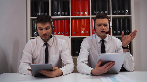 Two male in call-centre talking with customers by headsets Live Action