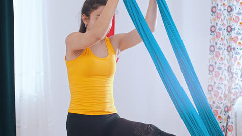Aerial yoga - a woman climbs in the hammock for yoga Live Action