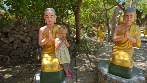 Little Girl Plays at Sitting Buddha Statues in Temple Park Live Action