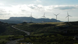 Wind turbines in the mountain together a road moving at cloudy day Footage