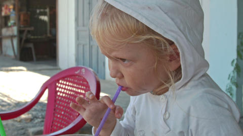Little Girl Sits at Table Drinks Juice in Sideroad Cafe Closeup Footage