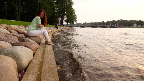 Woman sadly look to slow river waves, sit at stony bank, slow motion Footage