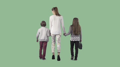 Young attractive mother with boy & girl are going from the camera. Alpha channel Live Action