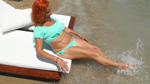 Youthful old woman in blue bikini having fun near the sea Live Action