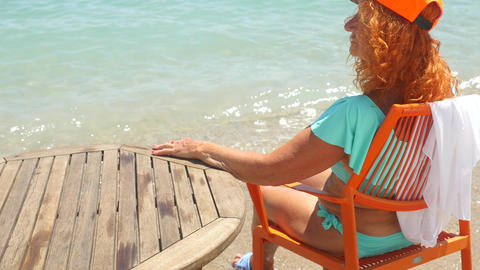 Youthful old woman in blue bikini relaxing by the sea Live Action