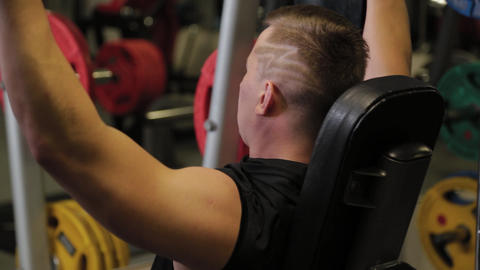 Professional athlete trains the shoulders with a barbell Live Action