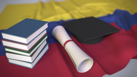 Graduation cap, books and diploma on the Colombian flag. Higher education in Live Action