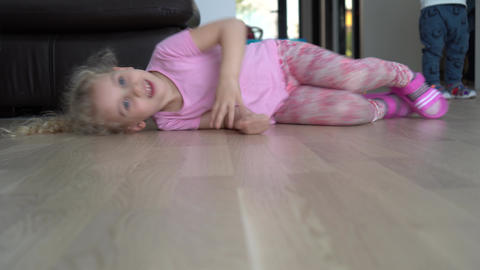 Playful girl romp on floor. Happy child have fun at home. Gimbal motion shot Live Action