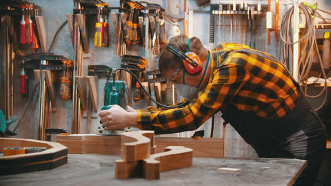 Carpentry indoors - a man woodworker polishes the plank in the workshop Live Action
