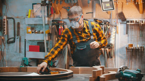 Carpentry indoors - a man woodworker put on a protective mask and soundproof Live Action