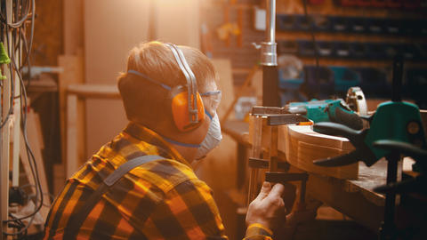 Carpentry indoors - a man woodworker measuring the thickness of wooden detail Live Action