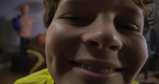 Extreme close-up face of joyful Caucasian boy with curly hair looking at camera Live Action