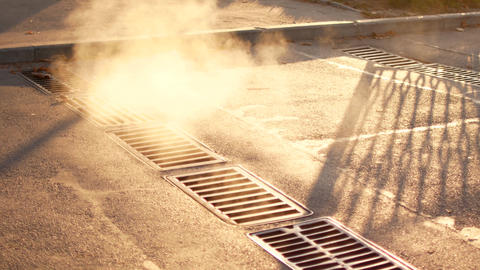 Steam from city drains. Morning in the city, steam comes from the city sewer Live Action