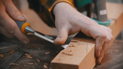 Carpentry - a woodworker cutting out the recess on the wooden block with a Live Action
