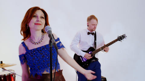 A musical band playing song in the bright studio - filming a music video Live Action