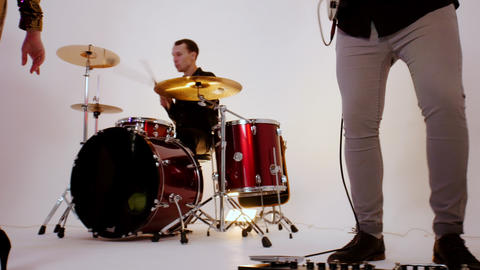 An emotional musical band playing song in the bright studio - filming a music Live Action