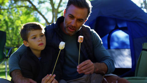 Father and son roasting marshmallows outside the tent Live Action