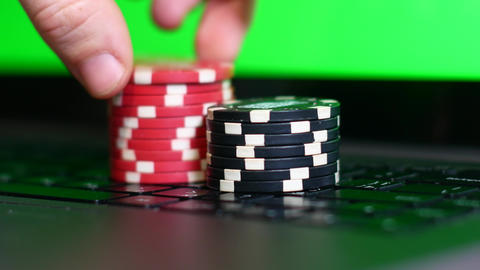 Chips for casinos on laptop, online casino concept Live Action
