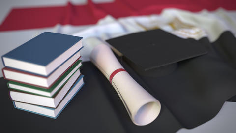 Graduation cap, books and diploma on the Egyptian flag. Higher education in Live Action
