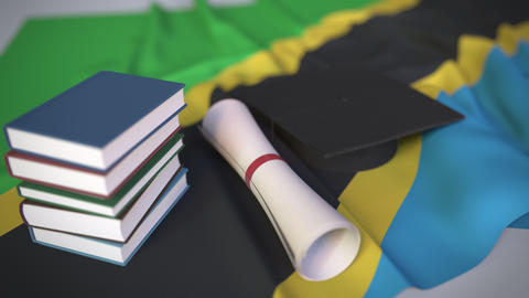 Graduation cap, books and diploma on the Tanzanian flag. Higher education in Live Action