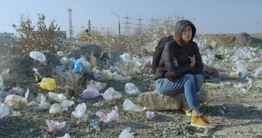 A girl sits in a place contaminated with plastic bags. The scale of the planet s Live Action