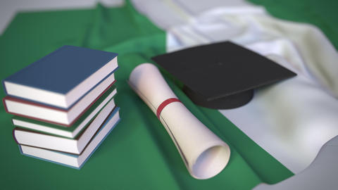Graduation cap, books and diploma on the Nigerian flag. Higher education in Live Action