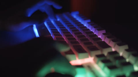 Male gamer typing and pressing keys on white gaming RGB keyboard in dark room Live Action