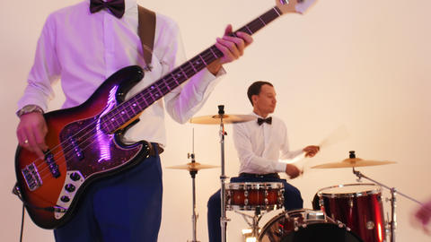 A musical band of four people in bright clothing playing song in the bright Live Action