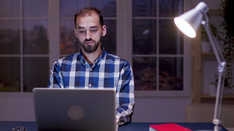 Thoughtful businessman typing on laptop while working late from home Live Action