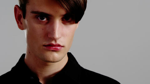 Androgynous man posing against grey background Live Action