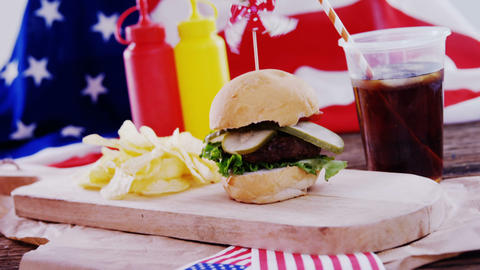 Hamburger and cold drink on wooden board Live Action