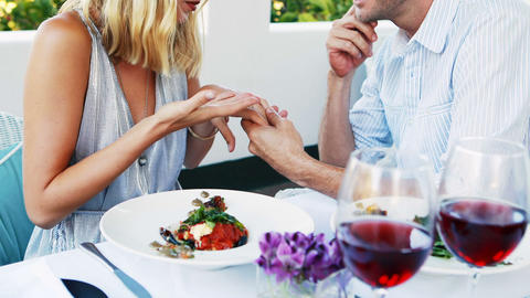 Man proposing woman while dining Live Action
