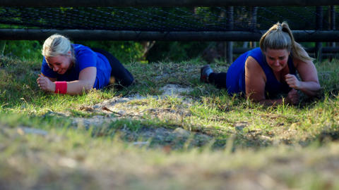 Determined women crawling under the net during obstacle course Live Action
