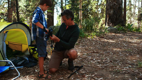 Father teaching son to use trekking pole outside tent Live Action